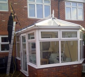 image of a man on a ladder cleaning a conservatory roog